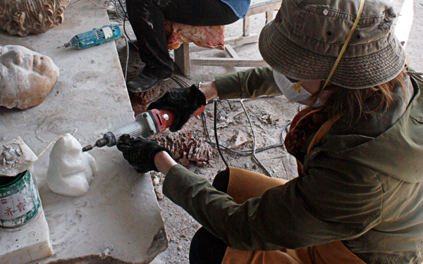 sculptor ellen scobie works on marble bear sculpture in china