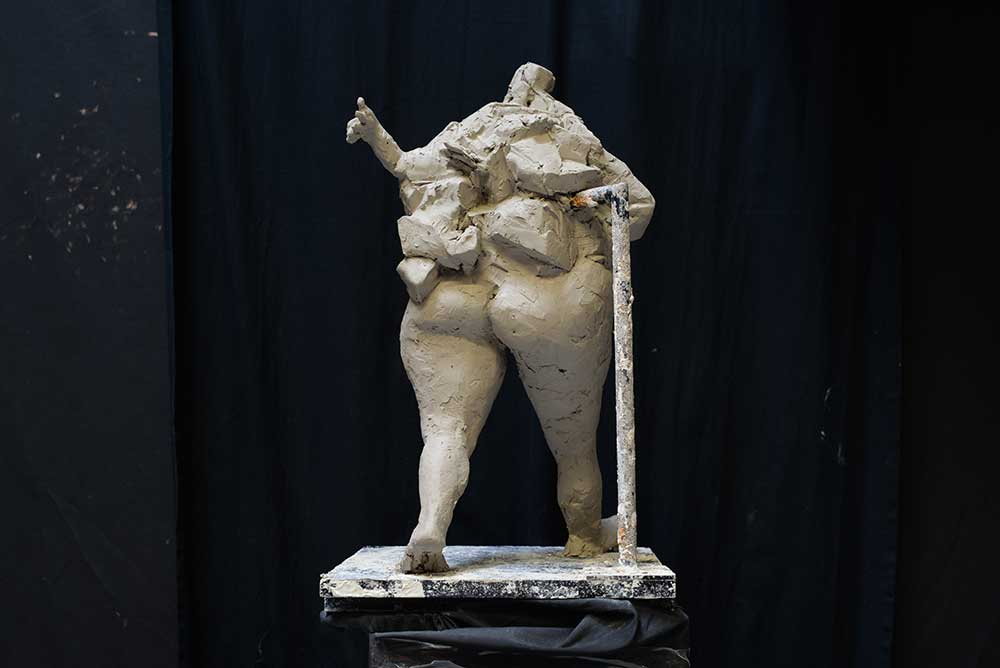 sculptural maquette in clay of walking figure with one arm out by Ellen Scobie