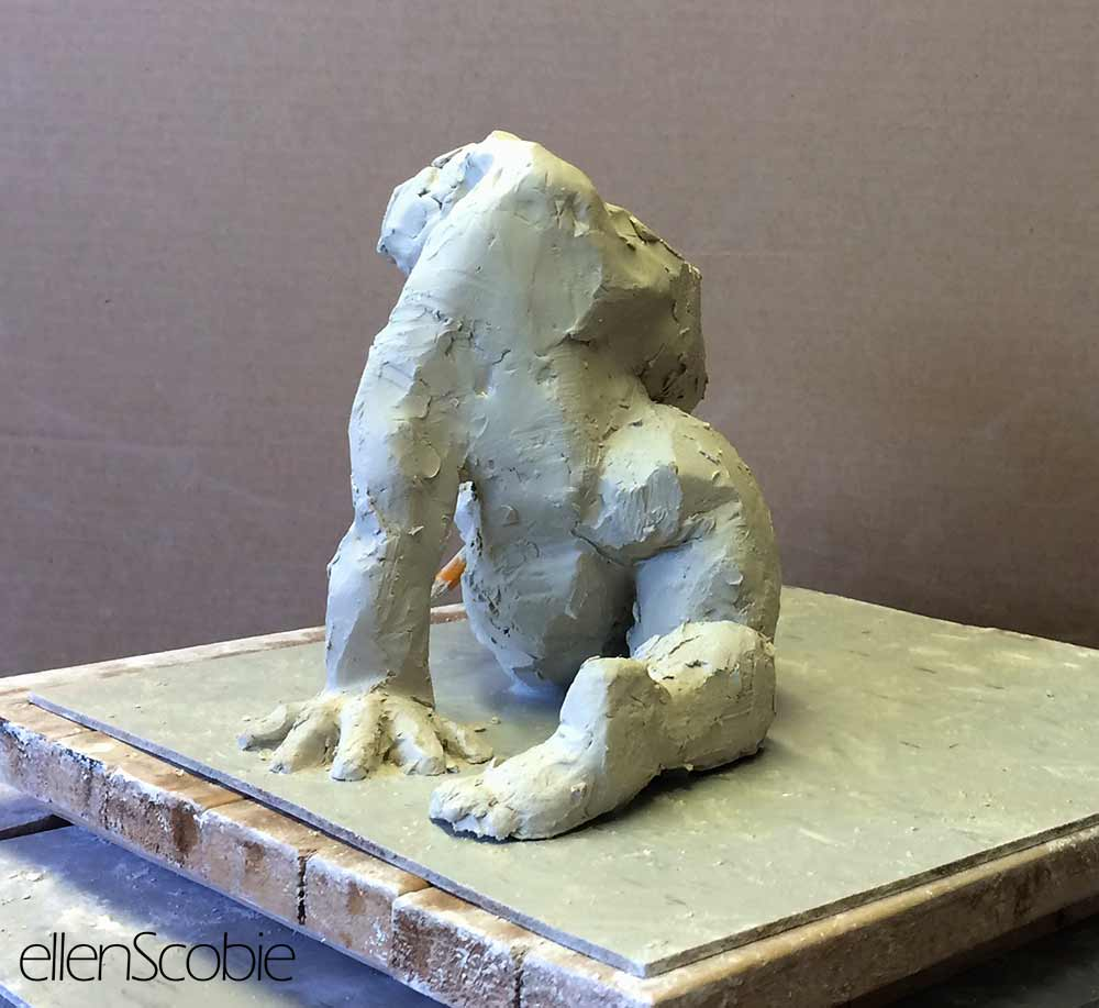 clay sculpture of kneeling figure on stand in artist studio