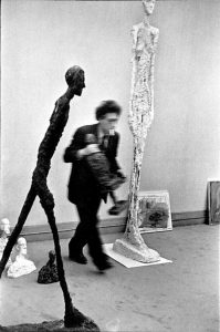 sculptor giacometti walking in his studio with his walking man sculptures, 1961 by Henri Cartier-Bresson