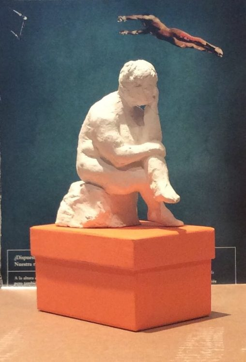 small terracotta seated figure with photo of trapeze artist behind